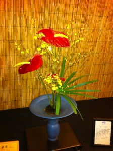 Red Anthuriums, yellow Oncidium Orchids and Papyrus are combined in an Ikenobo arrangement.